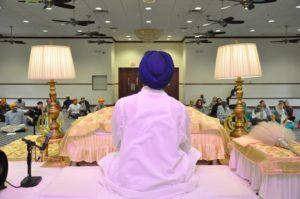 Sikh man sits behind Guru Granth Sahib in gurdwara.